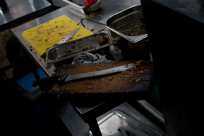 cutting boards of a street vendor, large knife in the foreground, bits of food