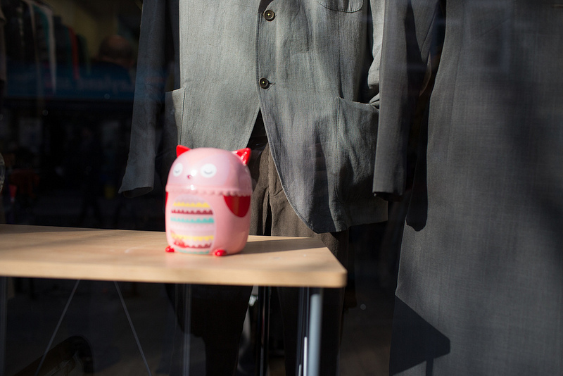 shop window display, pink plastic toy with fashionable grey clothing in the background
