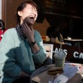 asian woman laughing, sitting at an outside table